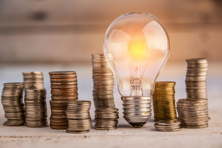 glowing light bulb among many coins heap business concept